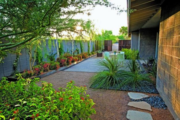 Dining patio with drought-tolerant plants lined along wall